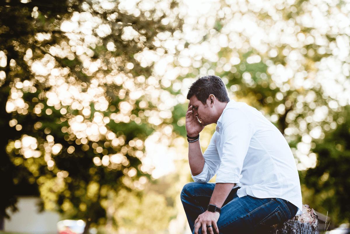 Un homme assis sur une pierre se tient la tête dans une main et pleure