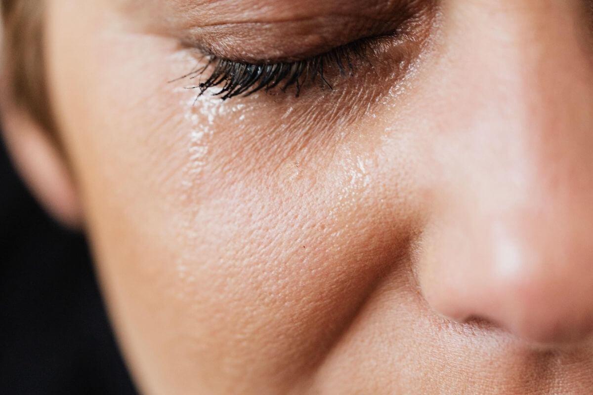 Une femme pleure une larme coule sur sa joue